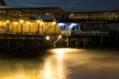海边餐馆在peop的木甲板突出物的晚上 免版税库存图片