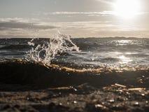 海边,波浪碰撞入在与蓝天的日落期间被夺取的shorebeach和海和没有人民海滩的 库存照片