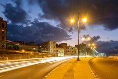 海边Malecon大道在哈瓦那在与交通足迹的晚上点燃 库存图片