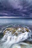 海运、岩石和泡沫在风雨如磐的天空下。 库存照片