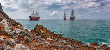 海运发运葡萄酒 岩石和海风景有美丽的多云天空和葡萄酒船的 图库摄影
