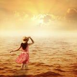海运和日落的愉快的妇女 免版税库存图片