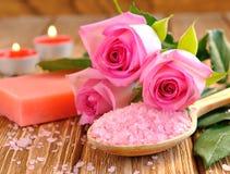 海运盐,玫瑰色,肥皂和一个灼烧的蜡烛 免版税库存图片