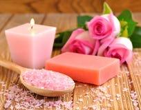 海运盐,玫瑰色,肥皂和一个灼烧的蜡烛 免版税库存照片