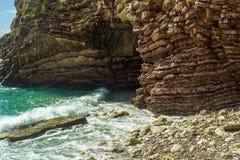海运视图 在石岸的波浪断裂 晃动并且分层了堆积石波浪结构、海泡沫和浪花 免版税库存图片