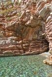 海运视图 对洞的入口从海 镇静清楚的海 岩石包括层状石头 黑山 库存图片