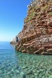 海运视图 对洞的入口从海 镇静清楚的海 岩石包括层状石头 黑山 库存照片