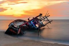 海难或被击毁的小船在海滩在suset 美好的横向 图库摄影