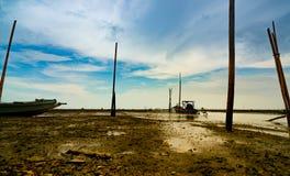 海风景浪潮的和蓝天和云彩与渔夫` s小船 海泥海滩,当水降下 停放的渔船 免版税库存图片