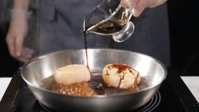 海鲜在餐馆 素食概念 倾倒在扇贝之上的手套的专业厨师调味汁在煎锅 慢 股票视频