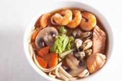 海鲜汤用面条和蘑菇虾,三文鱼,淡菜,红萝卜,莴苣 免版税图库摄影