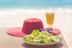 海鲜沙拉、橙色新鲜的汁液、帽子和太阳镜在桌上在海附近 免版税库存图片