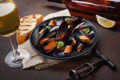 海鲜淡菜和蓬蒿叶子在一个黑色的盘子有酒瓶的,葡萄酒杯,拔塞螺旋,面包切片,粗麻布在生锈的背景 图库摄影