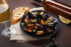 海鲜淡菜和蓬蒿叶子在一个黑色的盘子有酒瓶的,葡萄酒杯,拔塞螺旋,面包切片,粗麻布在生锈的背景 库存图片