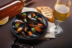 海鲜淡菜和蓬蒿叶子在一个黑色的盘子有酒瓶的,葡萄酒杯,拔塞螺旋,面包切片,粗麻布在生锈的背景 免版税库存照片