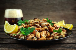 海鲜 蒸的Musseles开胃菜与洒在黑色的盘子服务的荷兰芹和柠檬juce与黑暗玻璃  免版税库存照片