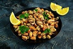 海鲜 蒸的Musseles开胃菜与洒在黑色的盘子服务的荷兰芹和柠檬juce 库存图片