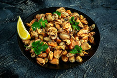 海鲜 蒸的Musseles开胃菜与洒在黑色的盘子服务的荷兰芹和柠檬juce 免版税库存图片