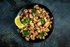 海鲜 蒸的Musseles开胃菜与洒在黑色的盘子服务的荷兰芹和柠檬juce 库存照片
