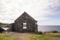 海鳗通过废墟墙壁被观看的峡湾海岸  图库摄影