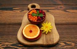 海鼠李和蔓越桔与薄菏叶子在切片桔子附近 免版税库存照片