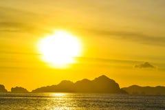 海,波浪,小山通过云彩阐明了阳光在日落 El Nido巴拉望岛菲律宾 免版税库存照片