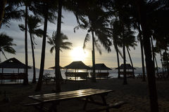 海,海滩,波浪,棕榈树丛通过云彩阐明了阳光在日落 El Nido巴拉望岛菲律宾 免版税库存照片
