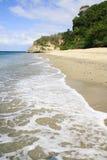 海滩、透明的水、蓝天和岩层画象视图  库存照片