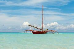 海洋与蓝色海和天空的夏日视图与白色云彩和红色小船 免版税图库摄影