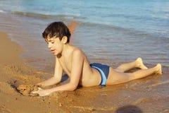 海滩作为日光浴戏剧的男孩与沙子 免版税图库摄影
