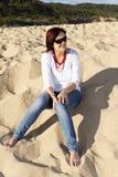 海滩佩带的太阳镜的妇女 免版税库存图片