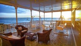海滨别墅日落的大阳台休息室 库存照片