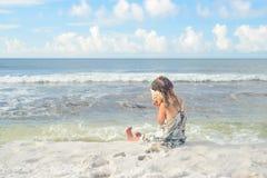 海滩听的贝壳的女孩 免版税库存照片