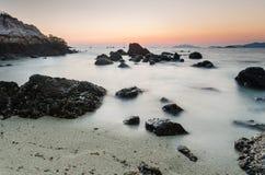 海滩和岩石在日落前 免版税库存图片