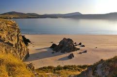 海滩和岩石峭壁在晚上太阳 免版税库存图片
