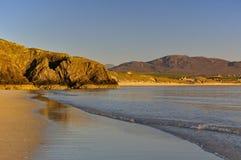 海滩和岩石峭壁在晚上太阳 图库摄影