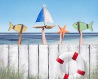海滩和木板条篱芭用拿着玩具的手 免版税库存照片