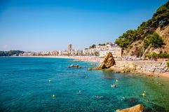 海滨和背景的一个镇全景与岩石峭壁的 库存照片