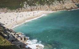 海滩和绿松石在Porthcurno浇灌在康沃尔郡 免版税库存照片