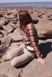 海滩坐的妇女年轻人 免版税库存照片