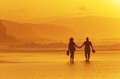 海滩夫妇日落走 免版税库存照片