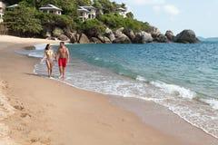 海滩夫妇走 走在海滩微笑的暂挂的新愉快的人种间夫妇在彼此附近 库存照片