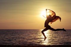 海滩女孩愉快跳 免版税库存照片