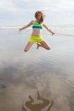 海滩女孩跳的年轻人 库存照片