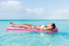 海滩妇女放松的晒日光浴的漂浮在海洋 免版税库存照片