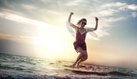 海滩妇女跳跃的暑假使变冷的概念 库存图片