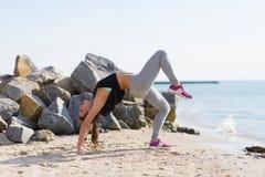 海滩实践的女子瑜伽 免版税库存照片