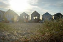 海滩小屋日落视图与沙子和草的在前景 免版税库存照片