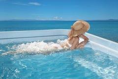 海滩帽子的妇女享用在极可意浴缸,在Tropica的游泳池的 库存照片