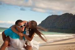 海滩愉快夫妇的乐趣有年轻人 免版税图库摄影